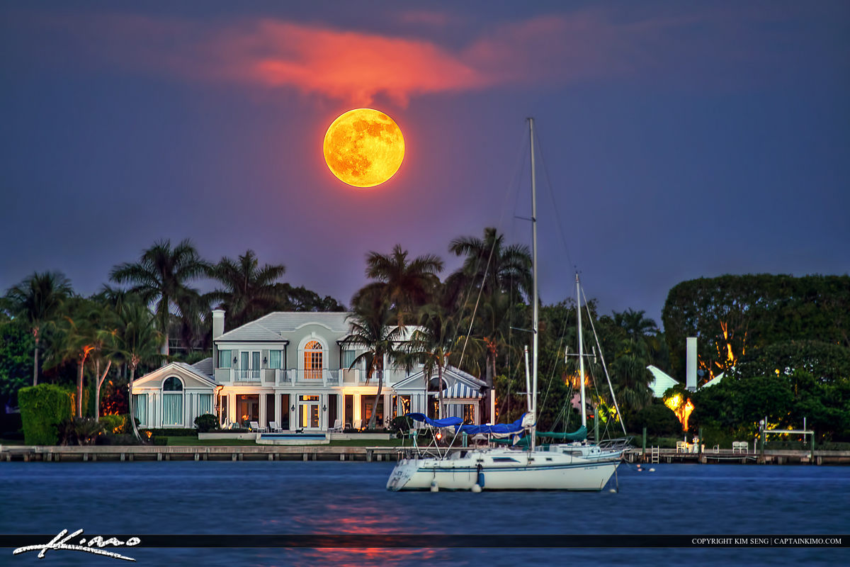Full moon rising over the Lake Worth Lagoon above waterfront house and sailboat.