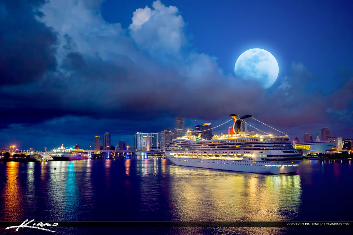 Night photo from Miami of the skyline during a full moon setting over the city along the port of Miami.