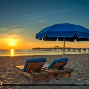 Sunrise at the beach in Lake Worth, Florida along the fishing pier with veach chairs and umbrella. HDR image created using Photomatix Pro and Topaz software.