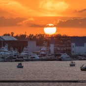 Large ball of sun setting over the New Port Marina in Rivera Beach, Florida in Palm Beach County along the waterway. HDR image merged in Adobe Lightroom and Topaz Denoise.