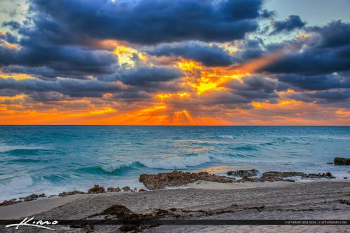 Beach Sunrise  with Sunrays Through Clouds along the Rocks